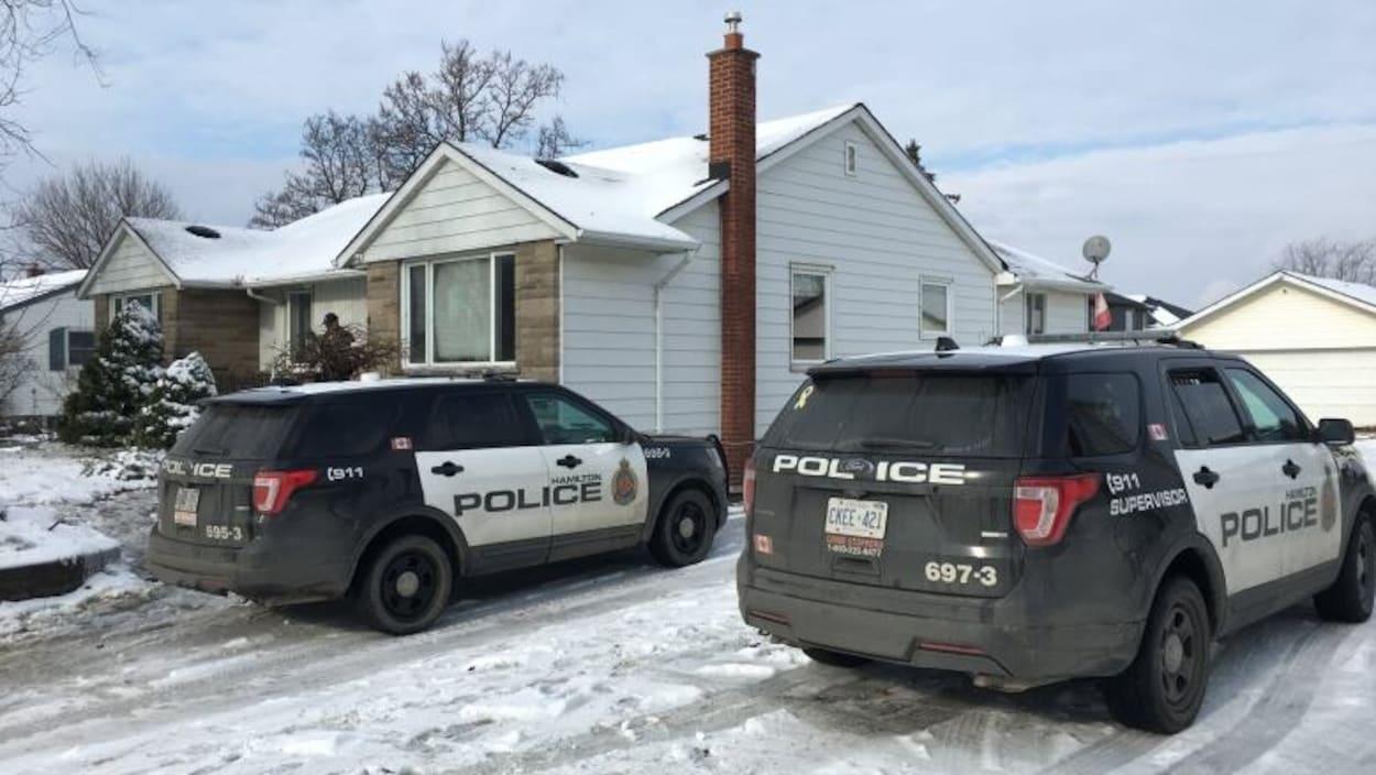 Deux voitures de police devant une maison en hiver.