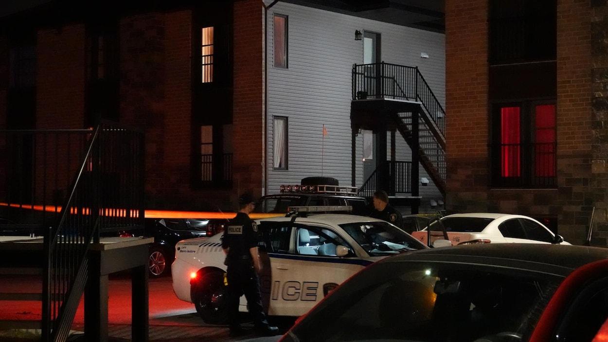 Des policiers se tiennent à côté de leur véhicule, stationné près d'un immeuble à logement.
