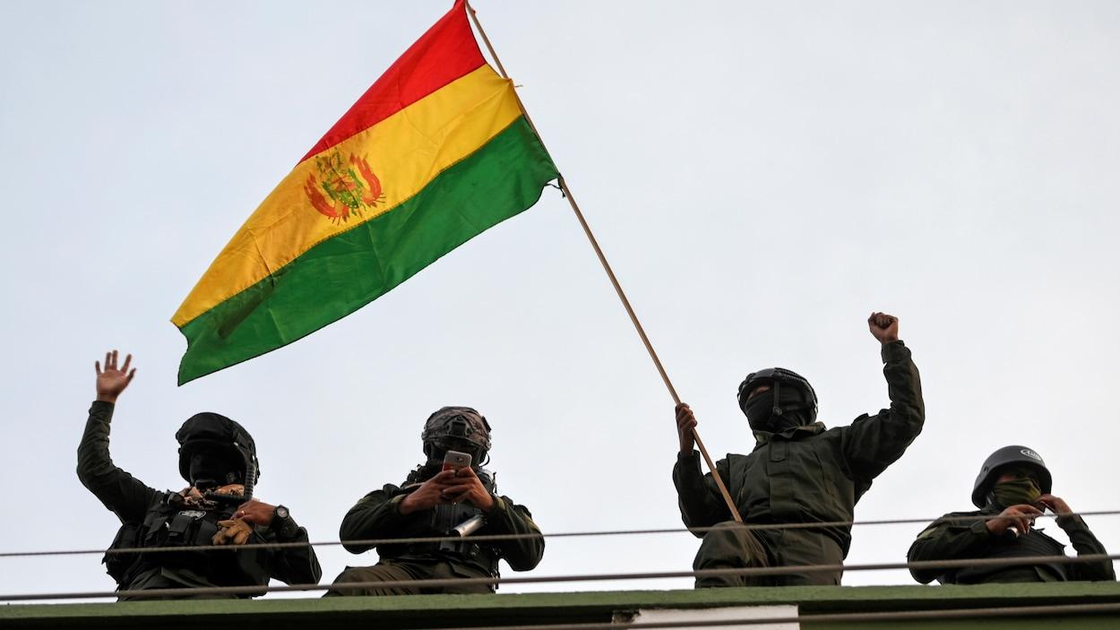 Des policiers masqués portent un drapeau bolivien.