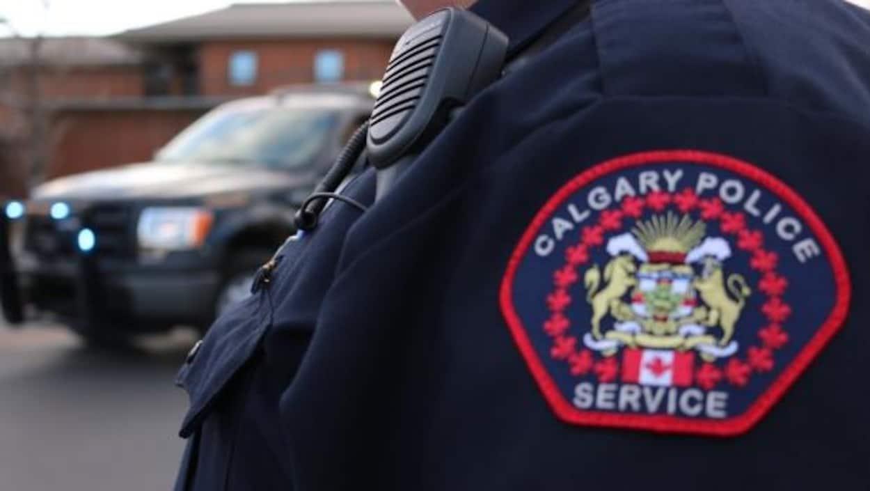 Photo en gros plan de l'écusson qui se trouve sur l'épaule d'un policier où il est écrit en anglais : Service de police de Calgary.