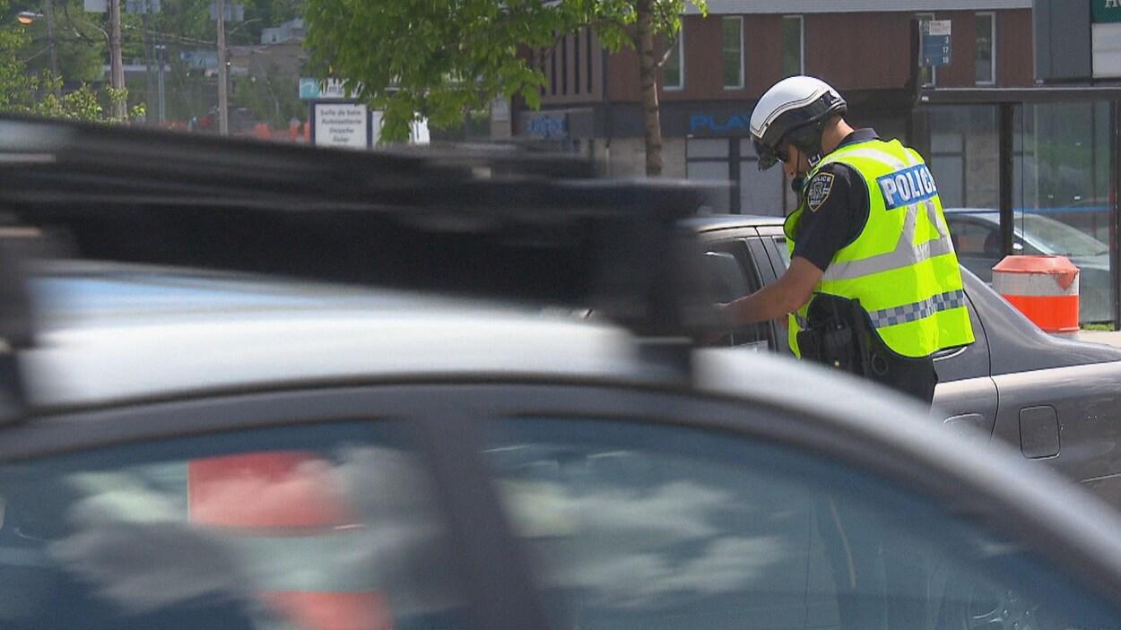 Un policier remet un constat d'infraction à un citoyen.