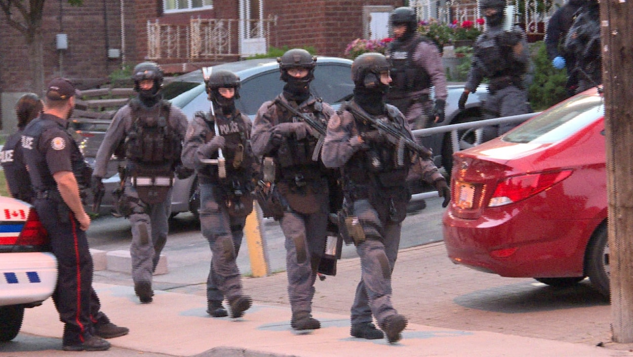 Photo d'agents de l'escouade tactique habillés en gris qui sortent d'un domicile.