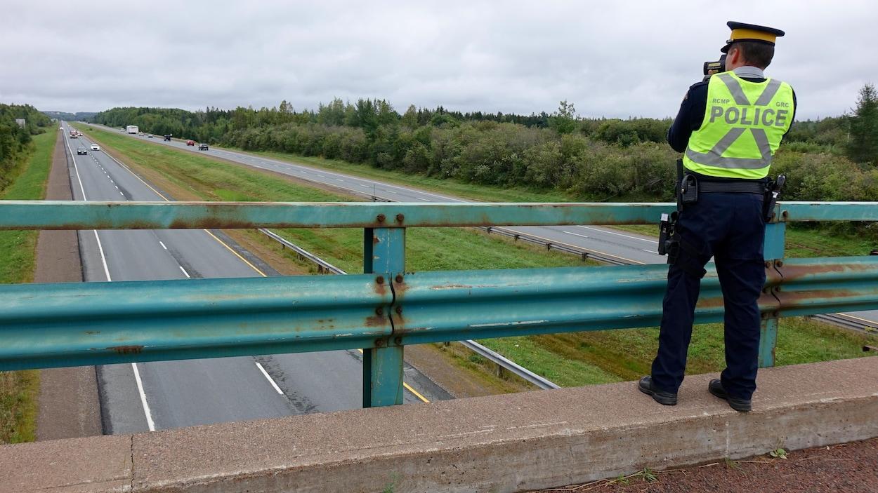 Un policier contrôle la vitesse d'automobilistes grâce à un radar photo.