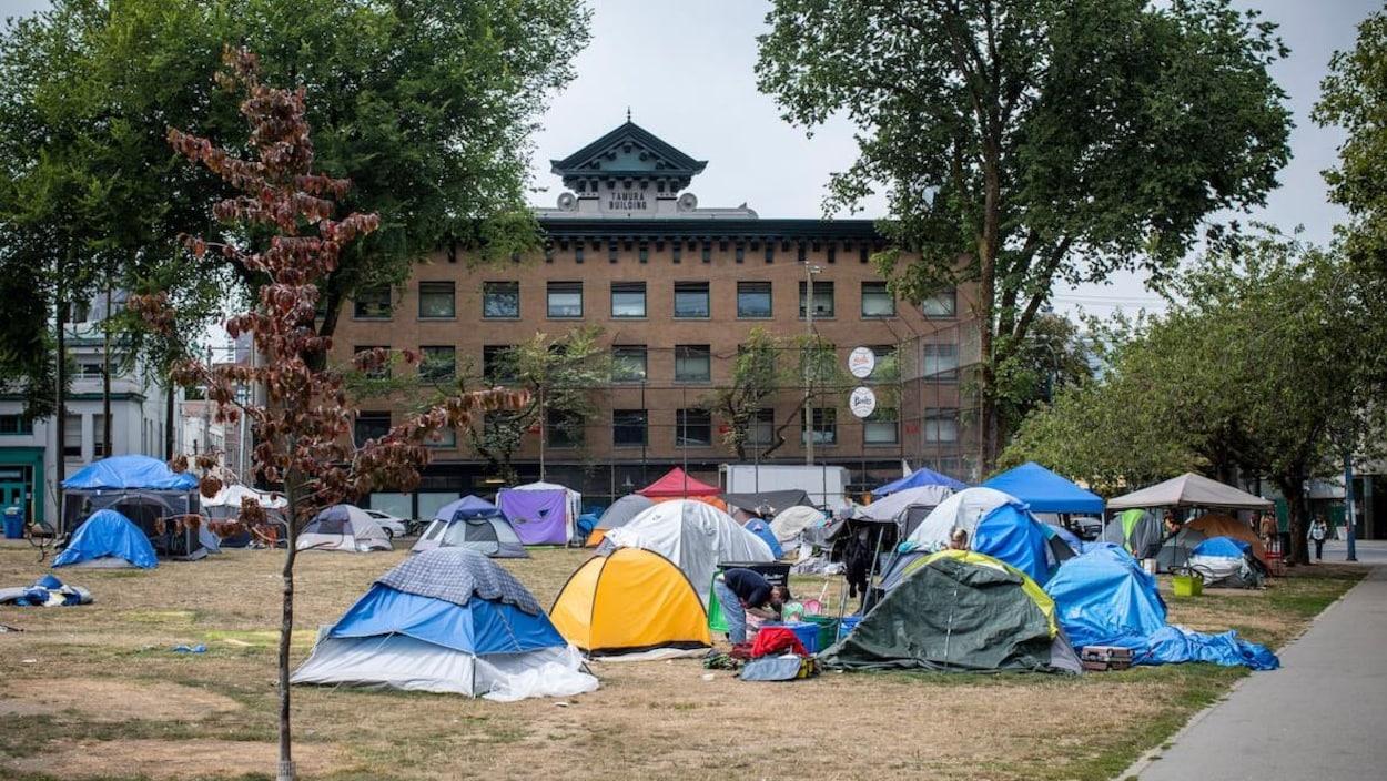 Des tentes dans un parc avec un édifice en arrière-plan.