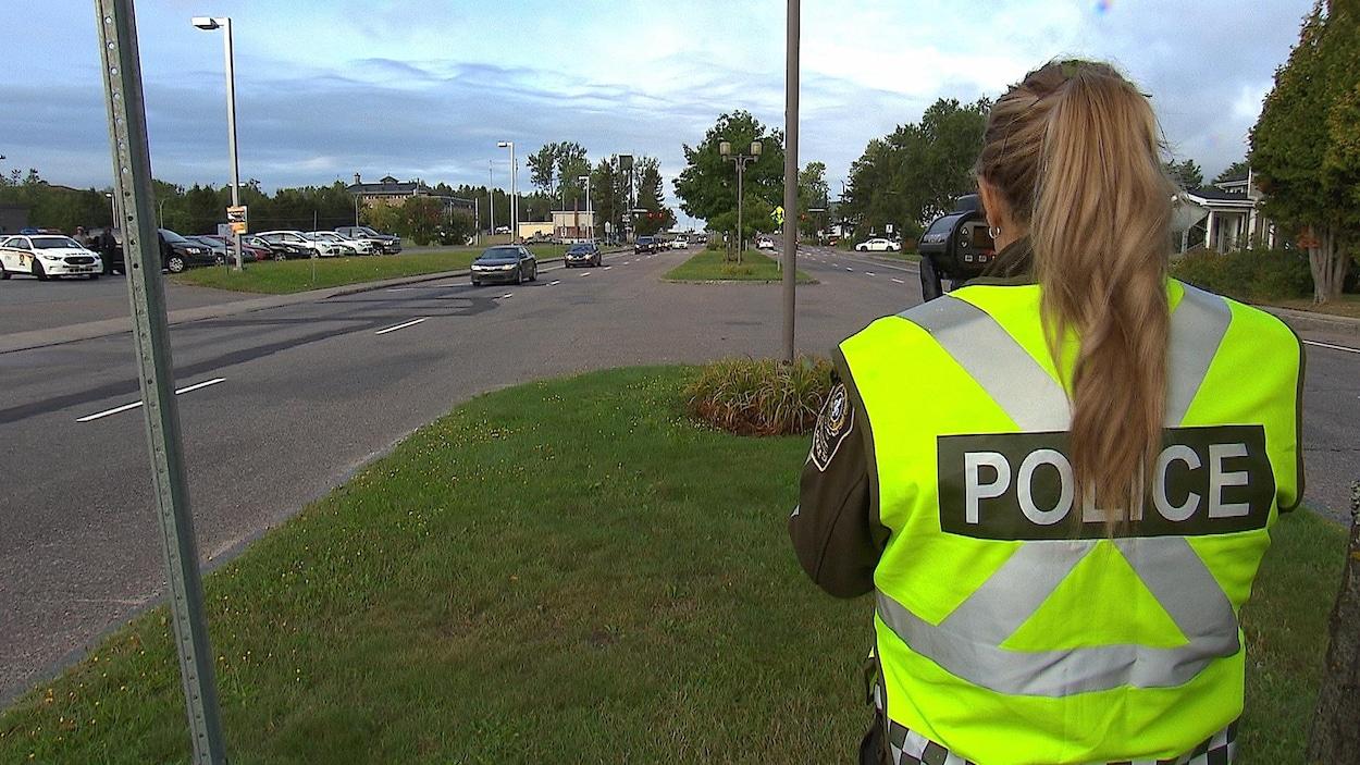 Une officière de police, un radar à la main
