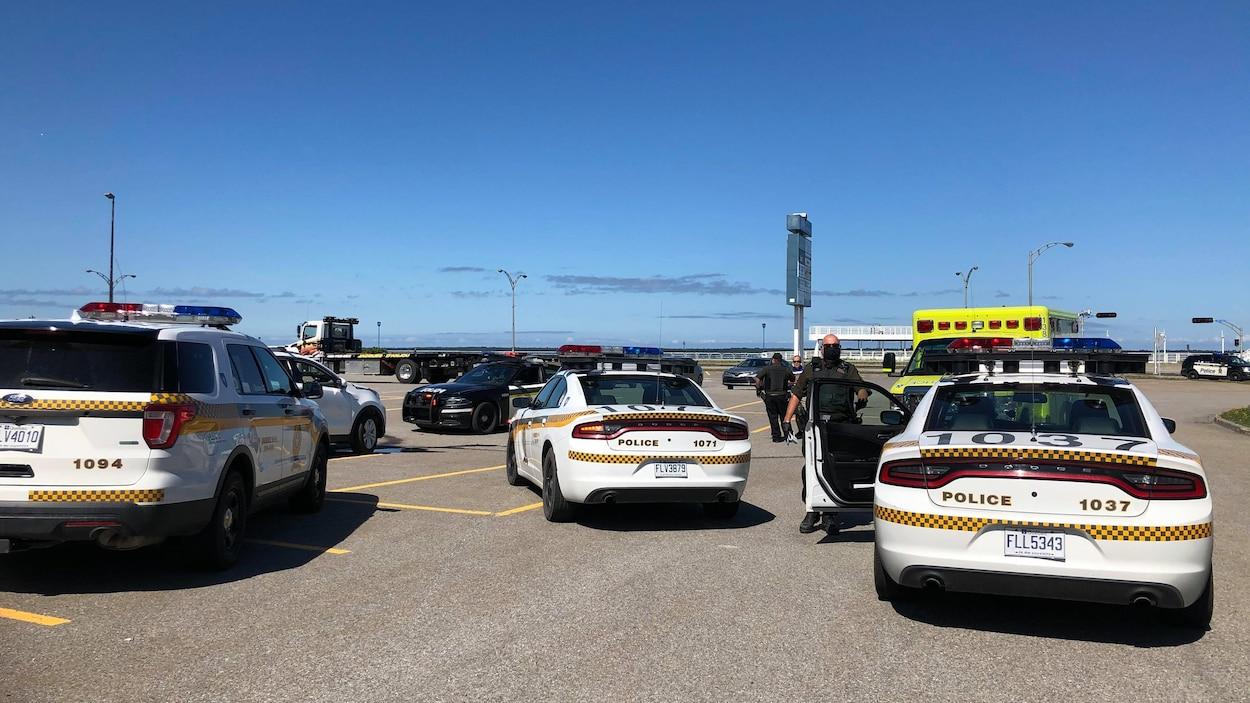 Quatre voitures de police et une ambulance dans un stationnement.