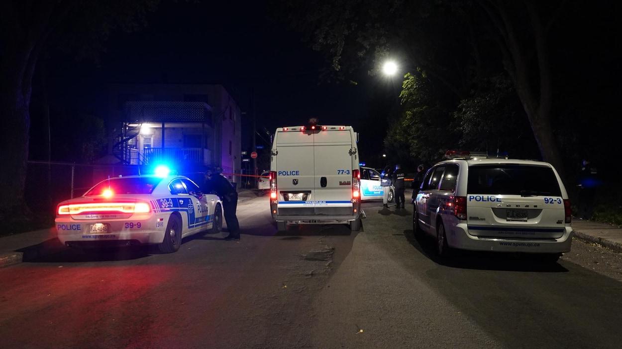 Des véhicules de police entourent un périmètre de sécurité. Il fait nuit.