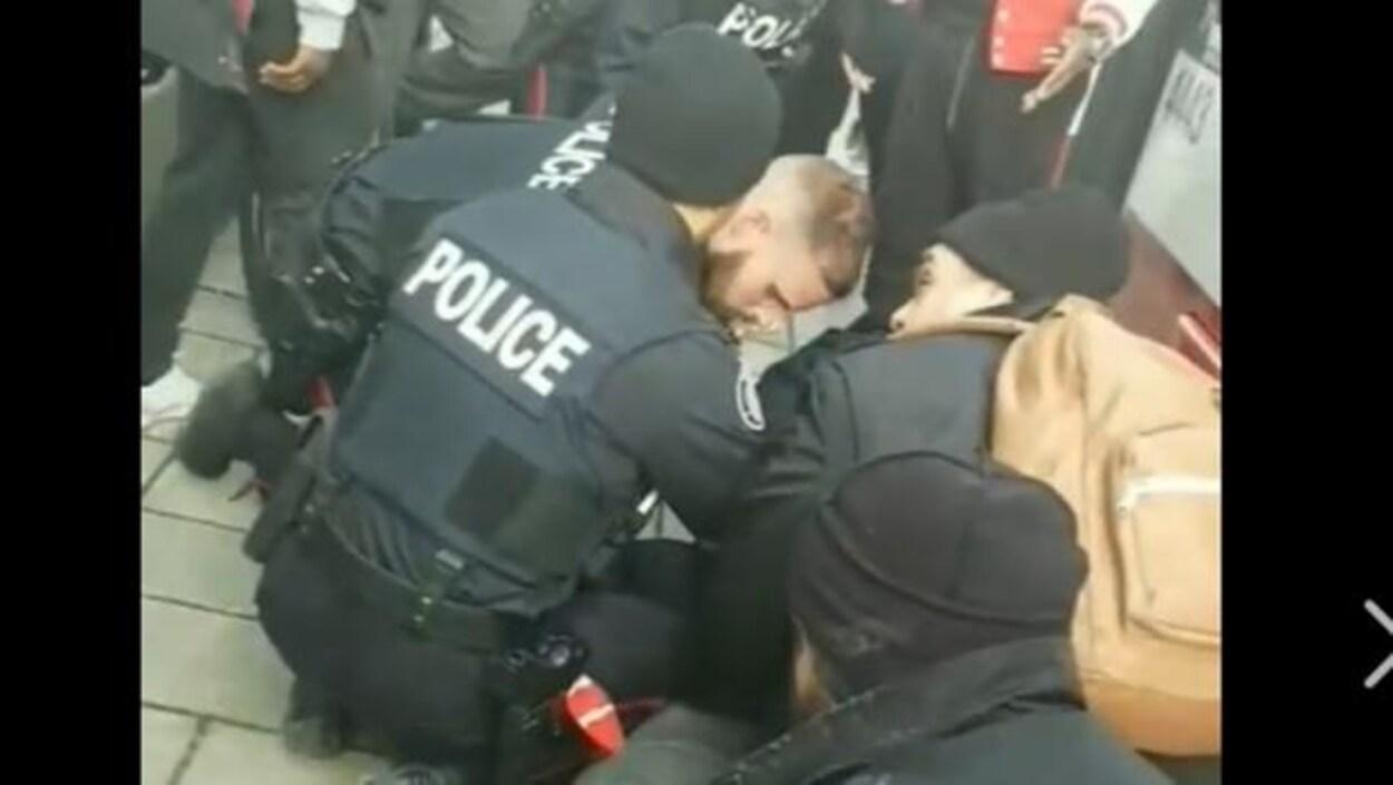 Les policiers maintiennent l'adolescent au sol.