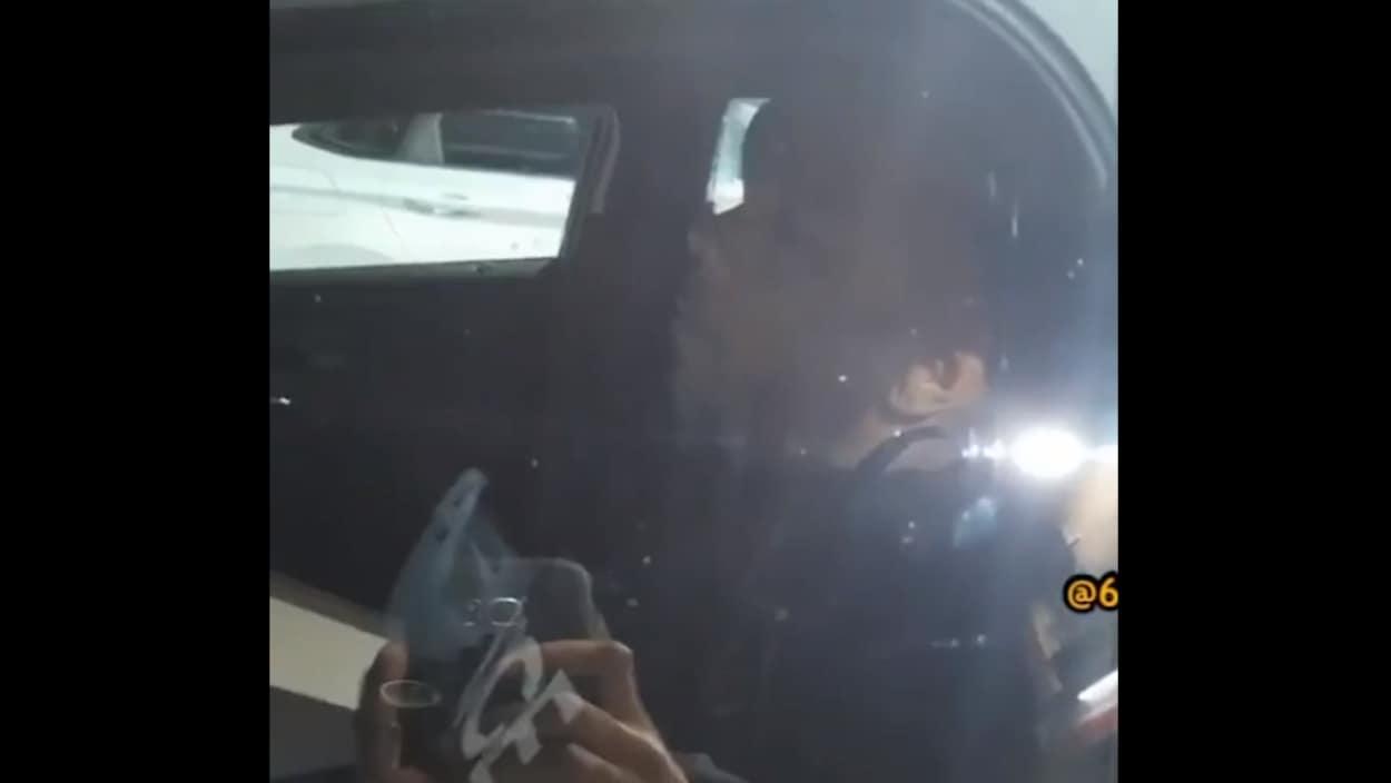 Un policier semble dormir dans une voiture de patrouille.