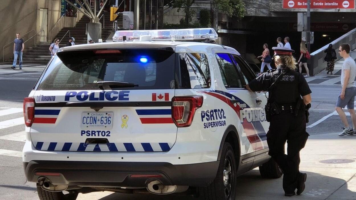 Une policière à côté d'un véhicule de police à une intersection du centre-ville.