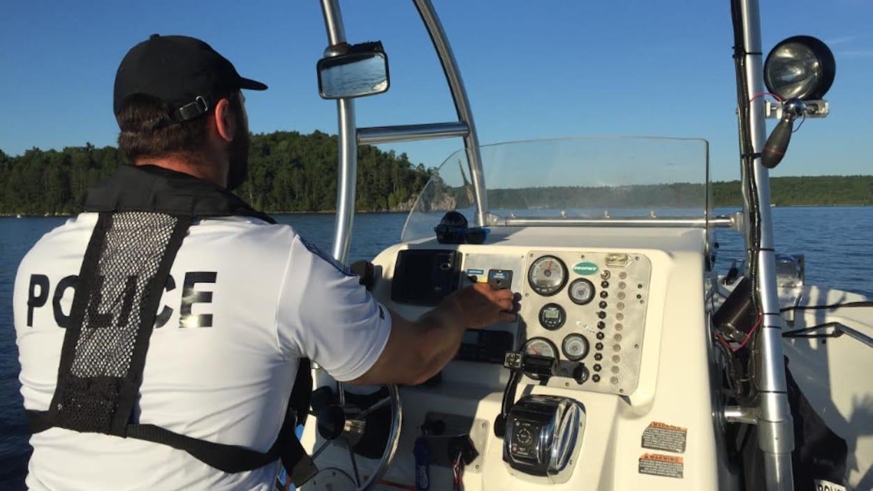 Un policier avec un chandail blanc identifié est au volant d'un bateau sur un cours d'eau.