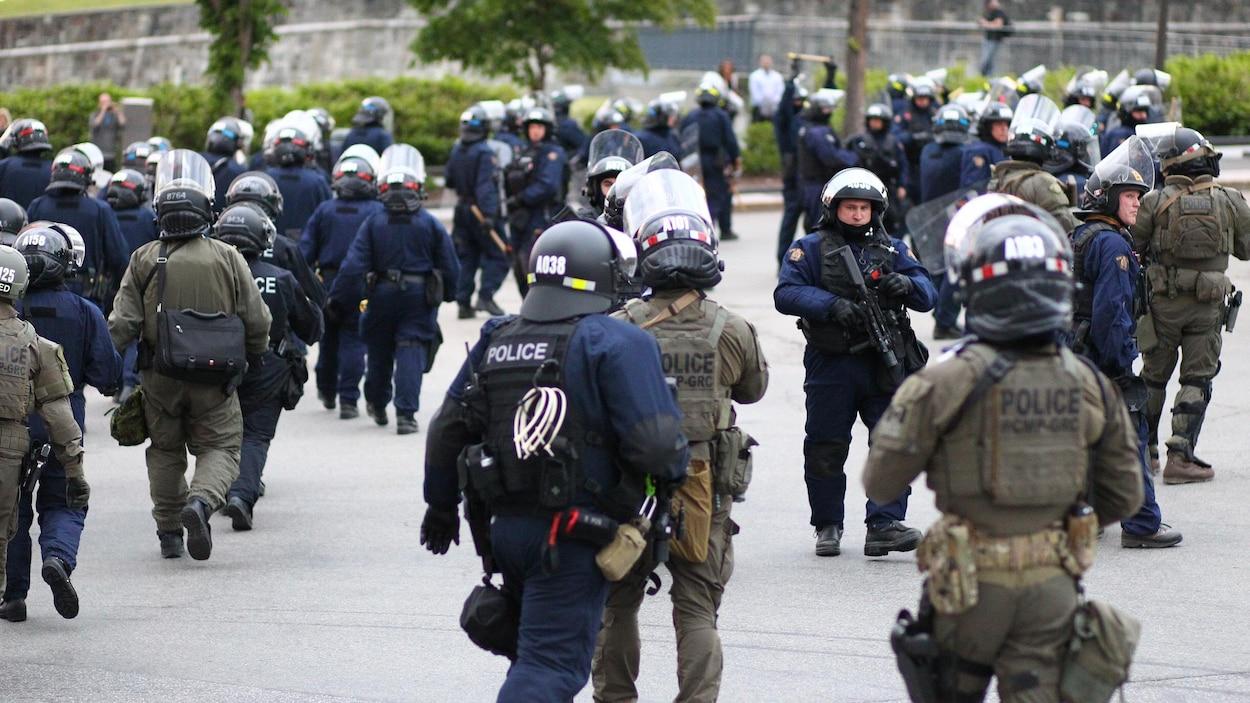 Des dizaines de policiers antiémeutes marchent à proximité des fortifications du Vieux-Québec.