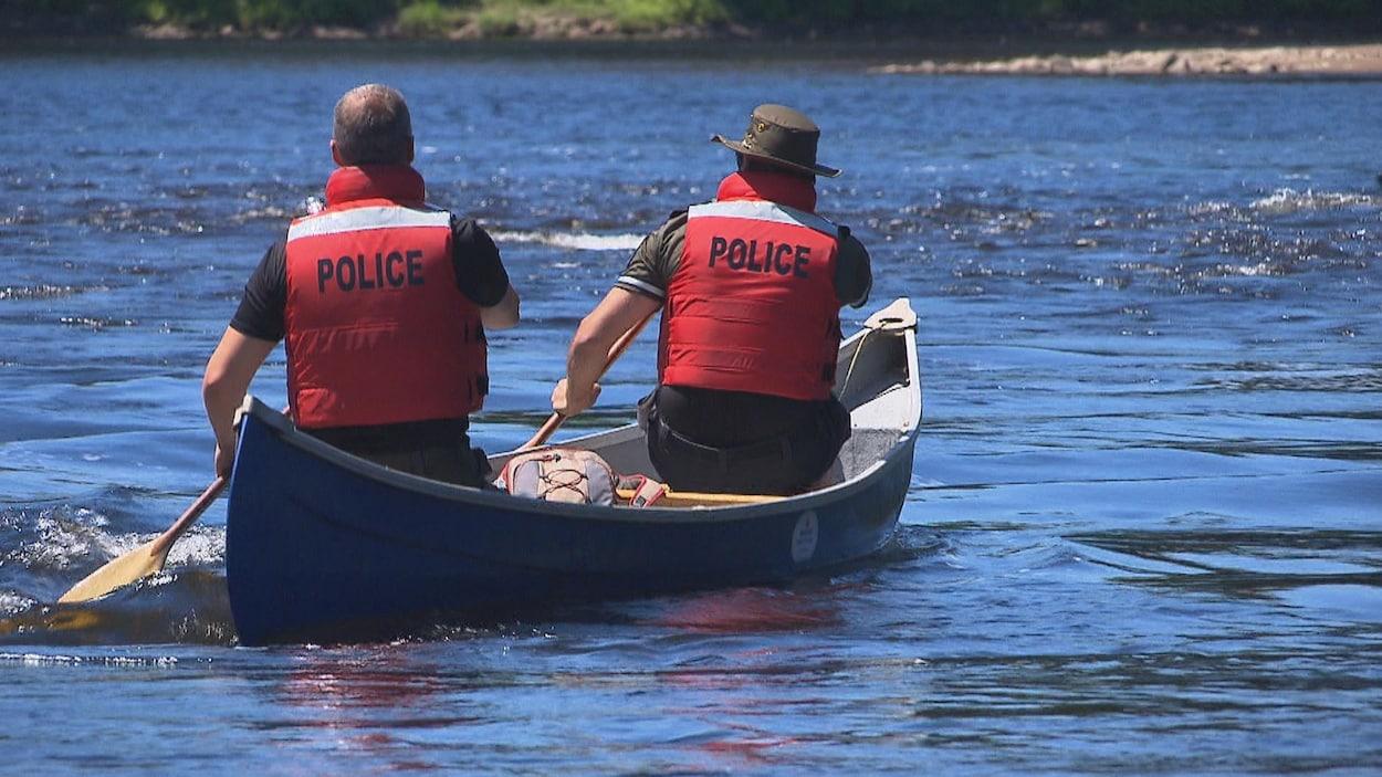 Deux policiers dans un canot sur une rivière.