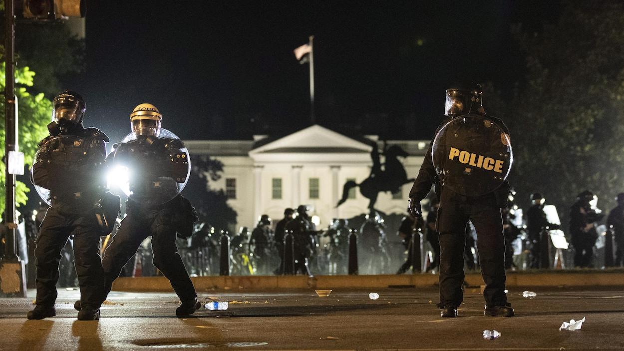 Des policiers en tenue anti-émeute, avec la Maison-Blanche en arrière-plan