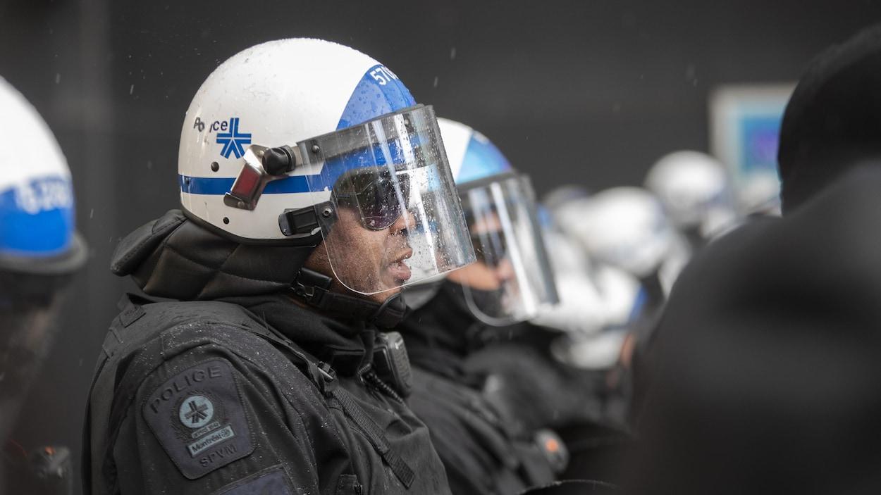 Des policiers côte à côte portant leur casque avec visière.