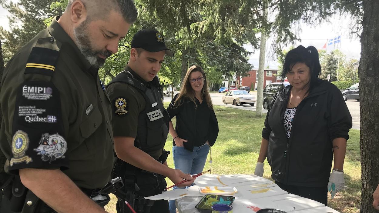 Des policiers du Poste de police communautaire mixte autochtone (PPCMA) de Val-d'Or participent à la confection de l'oeuvre collective au parc Bérard.