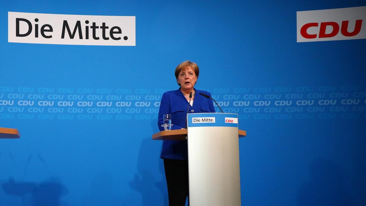 Angela Merkel lors d'une allocution, derrière un lutrin.