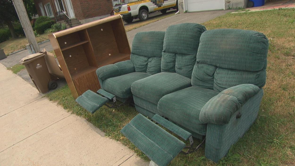 Des fauteuils et une bibliothèque sont laissés en bordure du trottoir.