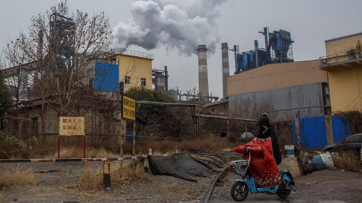 Une femme circule en scooter près d'une aciérie chinoise.