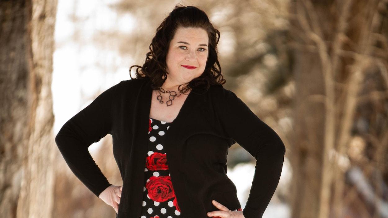 Une femme est dehors en petite robe soleil picotée noir et blanc, avec de grosses roses rouges.