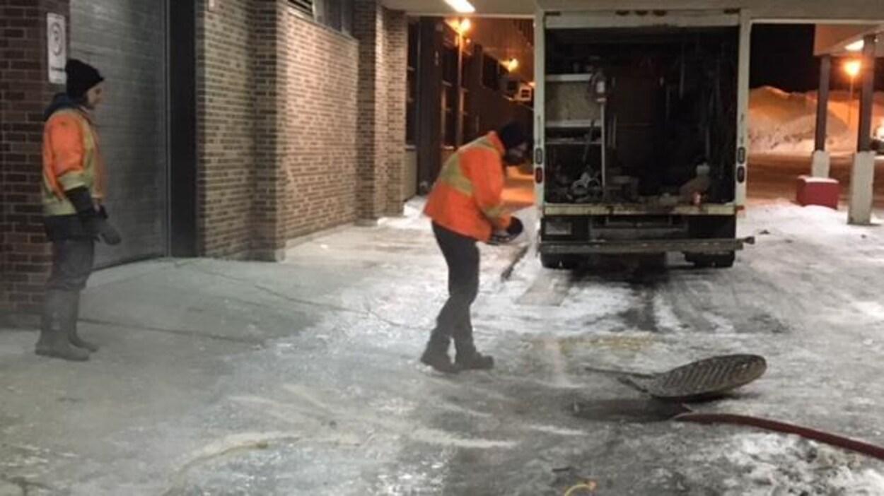 Des employés s'affairent pour réparer le bris d'aqueduc.
