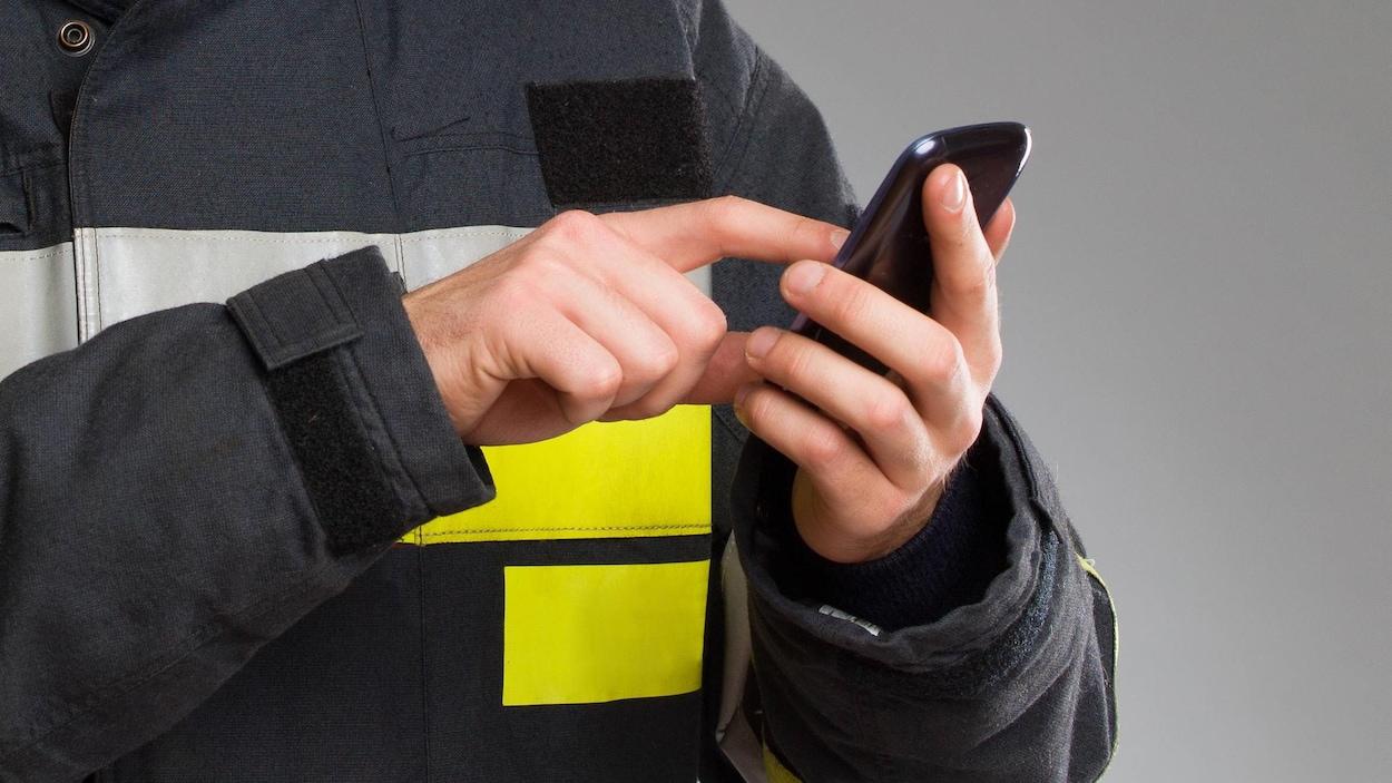 Un pompier utilise un téléphone cellulaire.