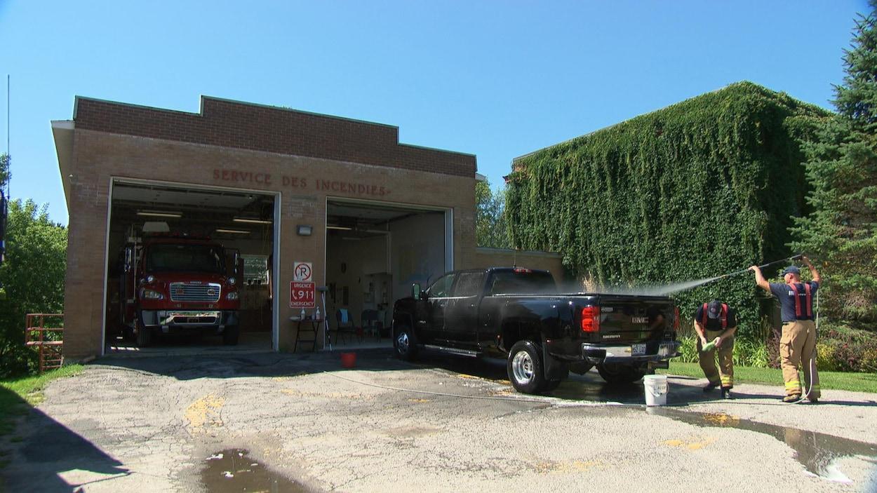 Deux pompiers lavent une camionnette devant une caserne de pompiers.