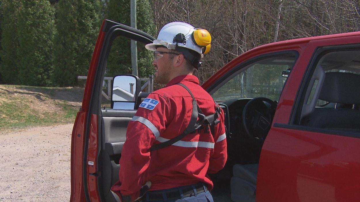 Un pompier de la SOPFEU se tient debout près de son véhicule.