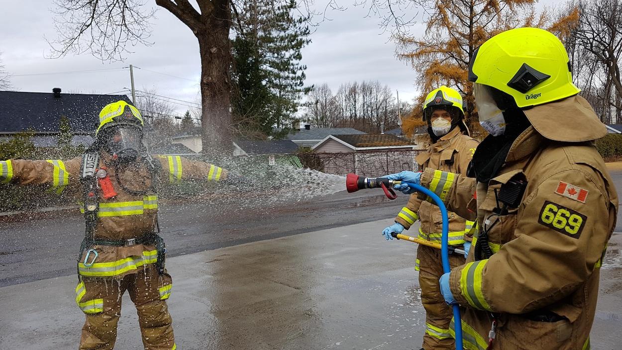 Un pompier rince l'équipement d'un collègue à l'aide d'un boyau d'arrosage sur les lieux d'un incendie.