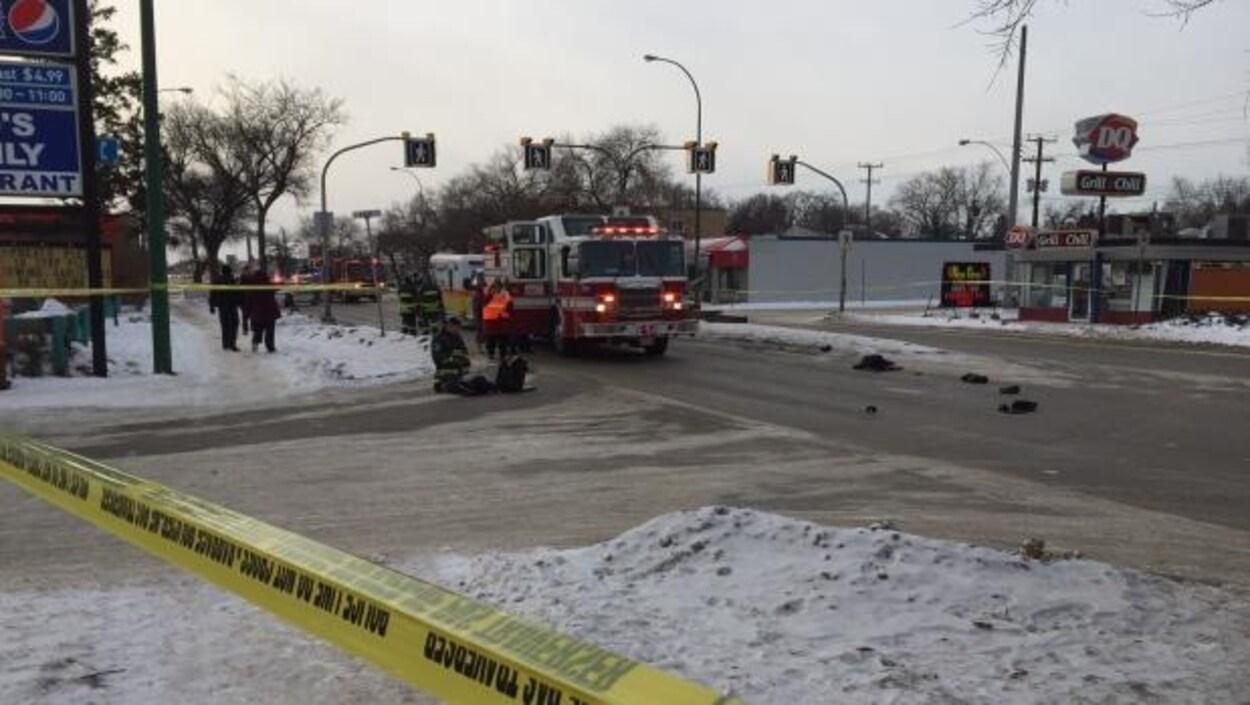 Des pompiers s'accroupissent devant un blessé au coin d'une rue entouré d'un périmètre de sécurité.