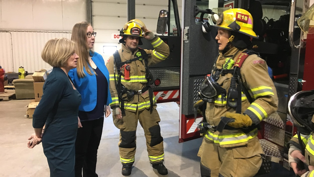 La première ministre Rachel Notley et la ministre du Travail Christina Gray parlent avec deux pompiers qui portent leur équipement de travail.