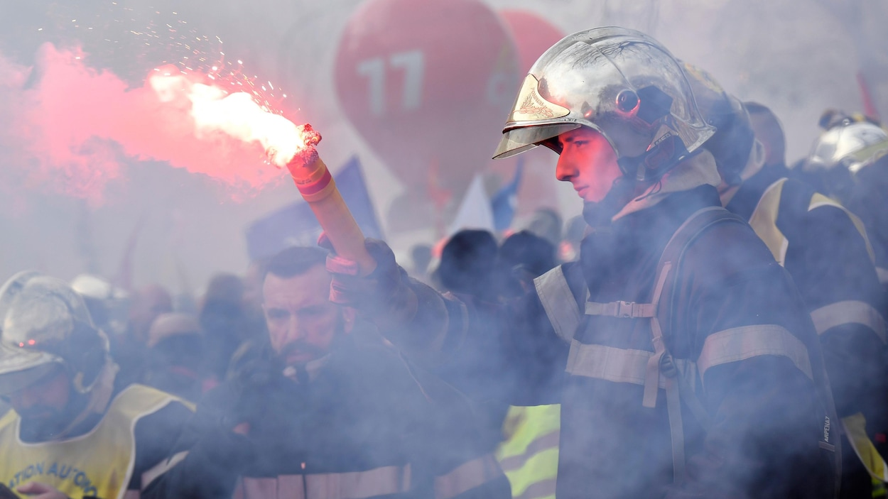Un pompier brandit une fusée de signalisation dans la rue.