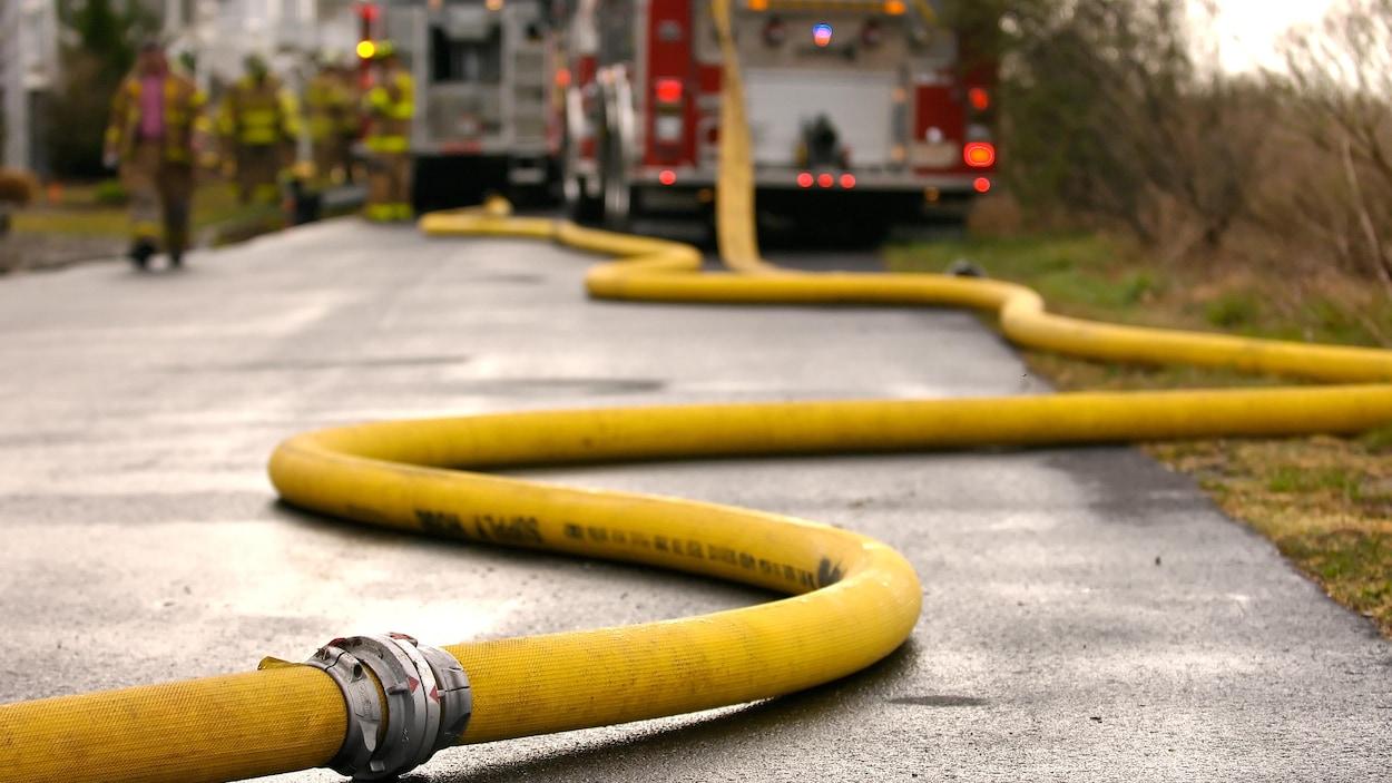 Boyau d'incendie sur le sol et pompiers en arrière-plan.