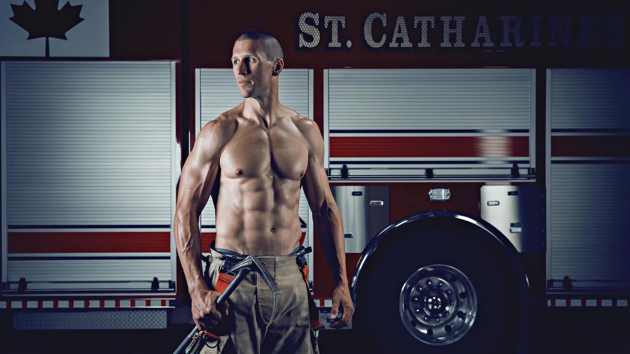 Une photo d'un pompier, torse nu et musclé, devant un camion du service d'incendie.