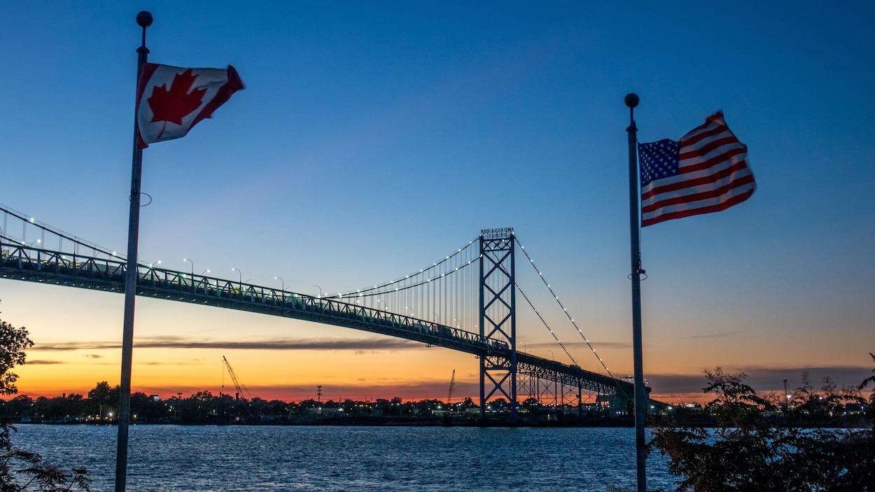 Une photo montre le pont Ambassadeur qui enjambe la rivière Détroit vu du côté de Windsor en Ontario avec les drapeaux canadien et américain.