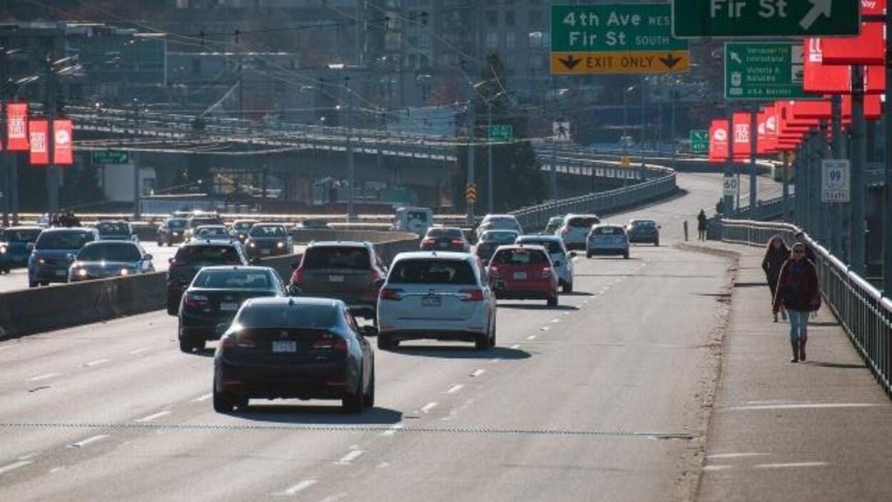 Quelques voitures circulent sur le pont Granville alors qu'une poignée de piétons y empruntent les trottoirs.