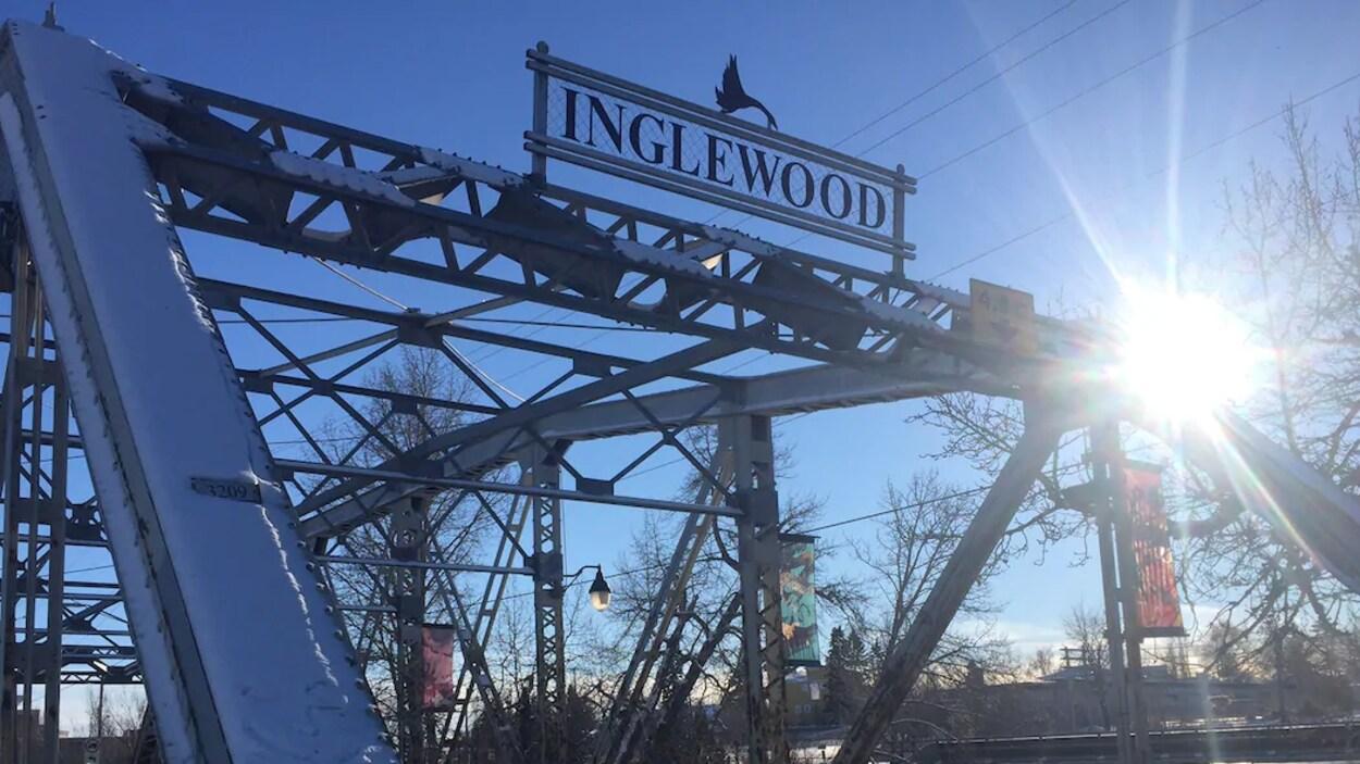 Une voiture noire passe sur un pont. Son nom, Inglewood, est inscrit sur le dessus de la structure.
