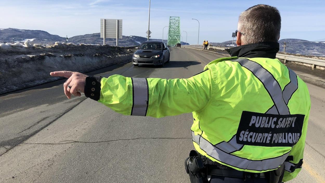 Un agent fait signe à un automobiliste.