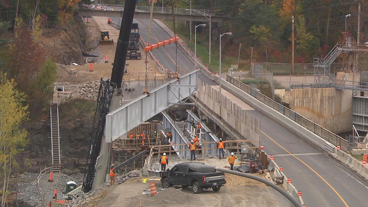 Une grue descend une poutre sur un chantier d'un pont qui surplombe une rivière.