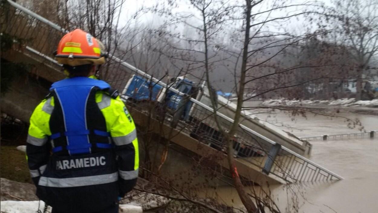 Un ambulancier en uniforme regarde un pont effondré dans une rivière. On voit un camion sur le pont.