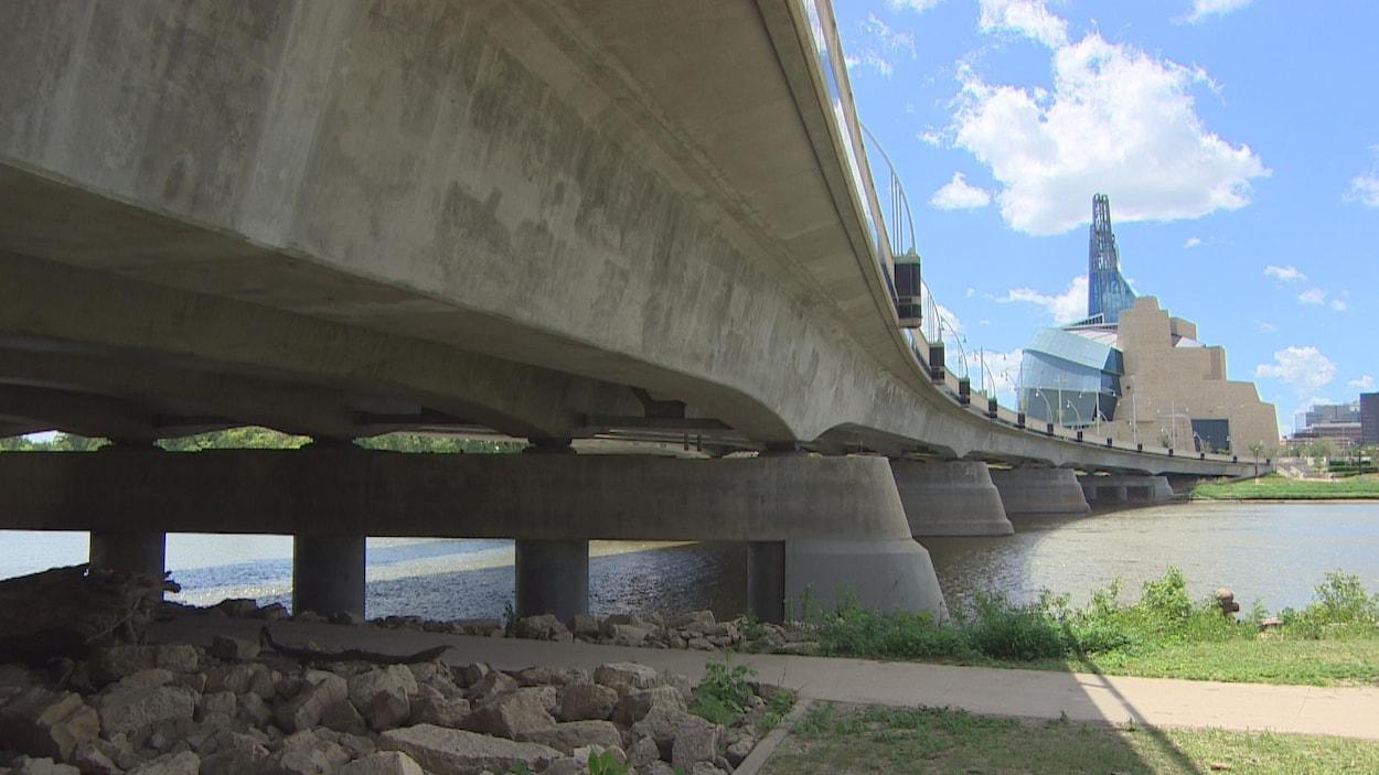 Un grand pont au-dessus de la rivière. Au fond, le Musée canadien pour les droits de la personne.