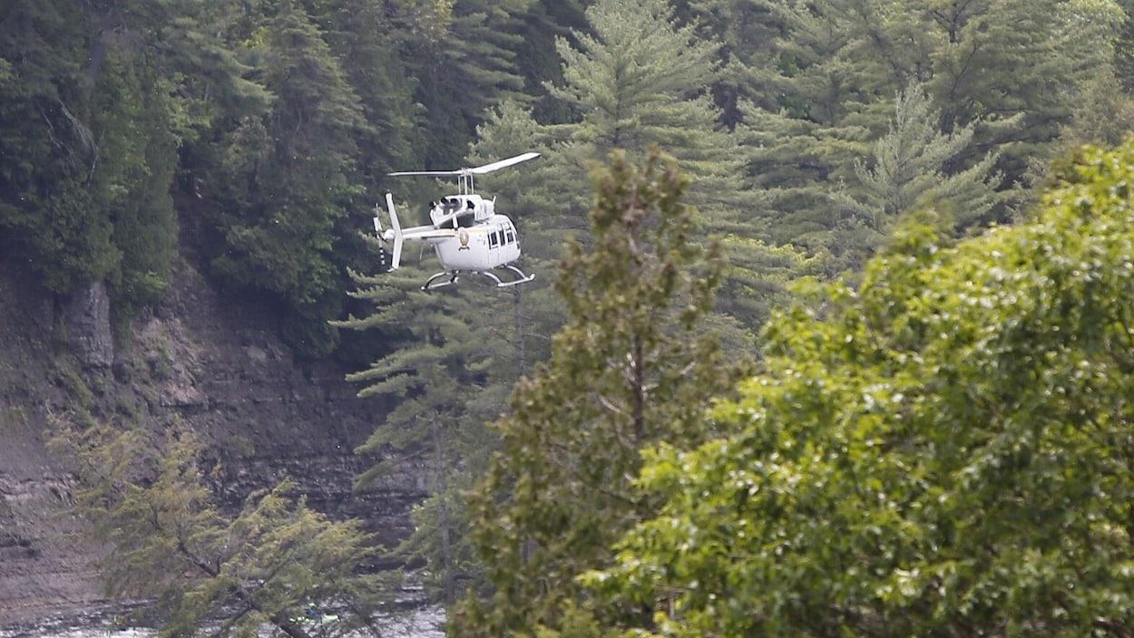 Un hélicoptère de la Sûreté du Québec survolant une rivière.