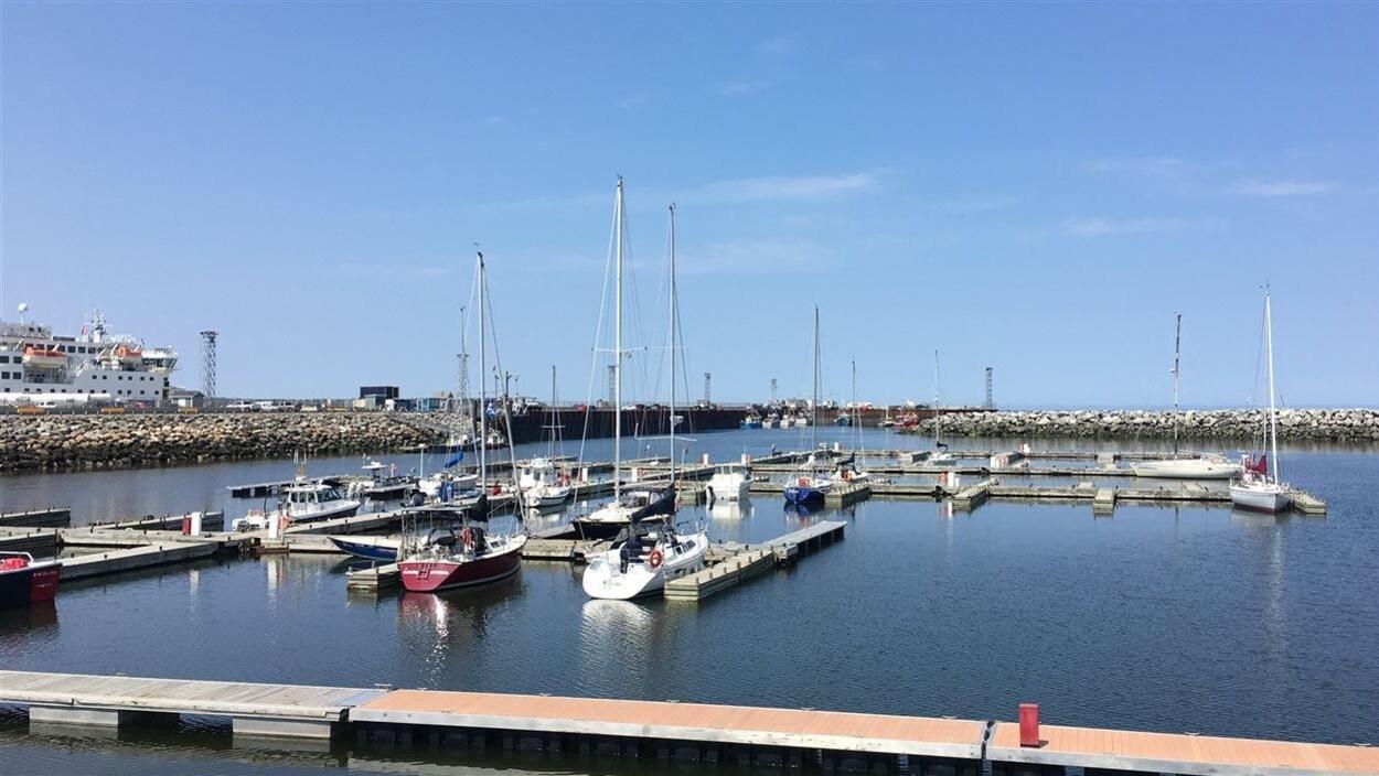 Vue d'ensemble de la marina avec ses pontons, quelques voiliers, l'enrochement et, au fond, le quai réservé à la pêche commerciale