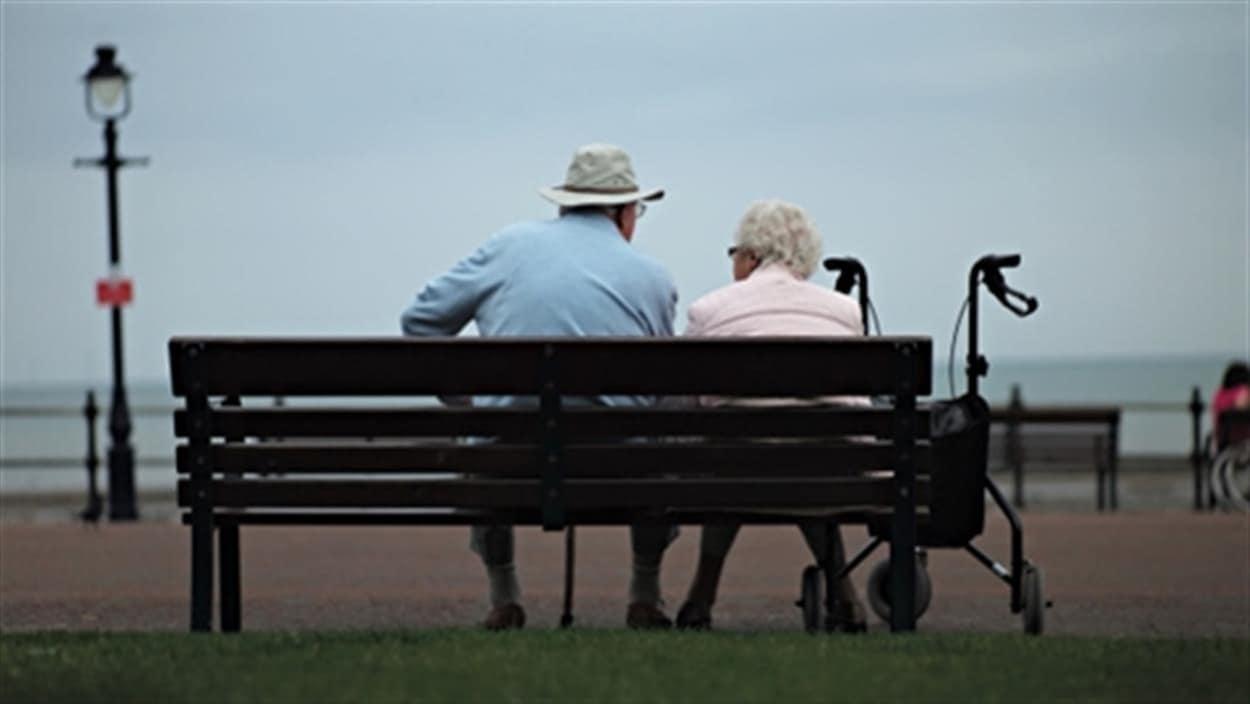 Deux personnes âgées, qu'on voit de dos, sont assises sur un banc devant la mer.