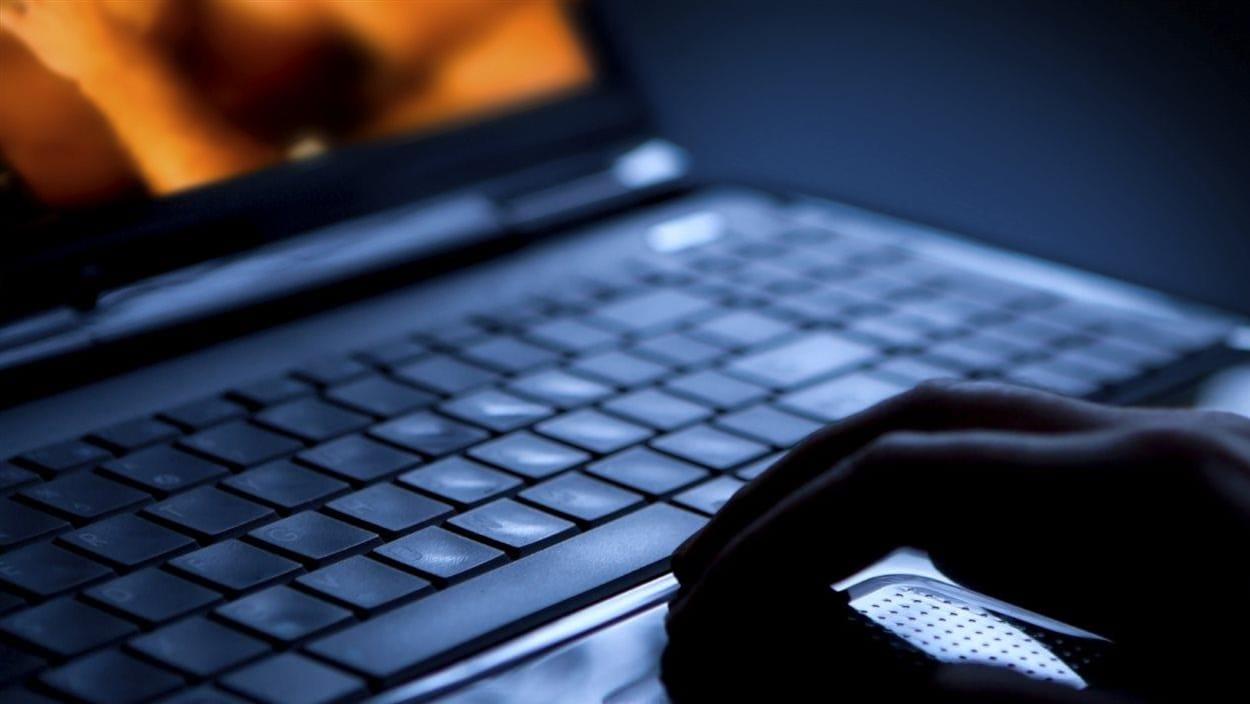 Une photo sombre montrant le clavier d'un ordinateur portable avec la main d'un homme posée dessus. On peut deviner que l'homme regarde de la pornographie sur l'écran.