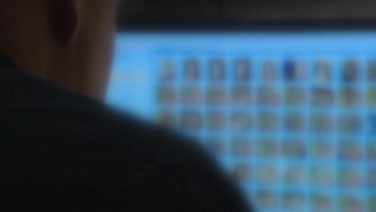 Image brouillée d'un homme qui regarde des photos sur un écran d'ordinateur.