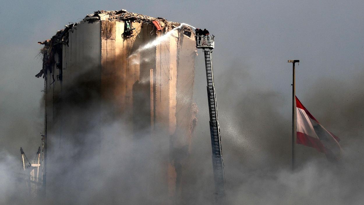 Des pompiers libanais tentent d'éteindre le feu dans le port de Beyrouth.