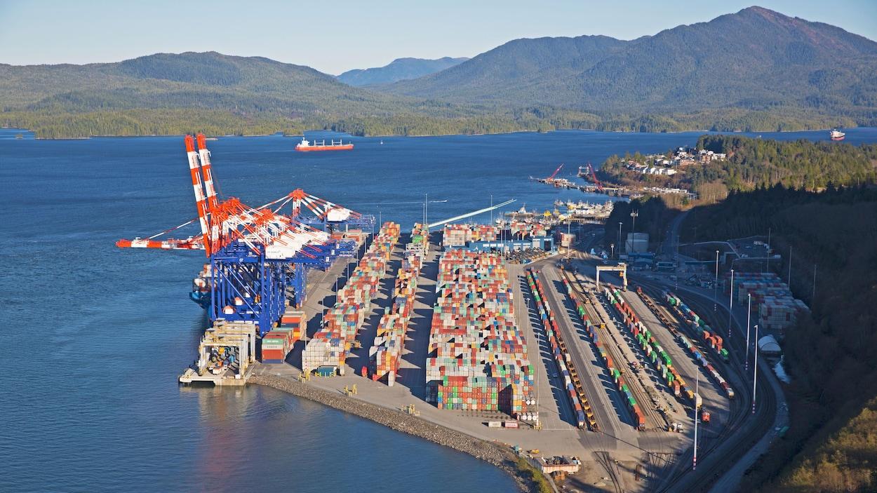 Vue aérienne du terminal Fairview, avec les grues du port, des rangées de conteneurs et des trains en chargement.