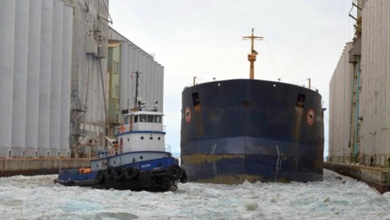 Un navire est escorté par un remorqueur dans le port de Thunder Bay.