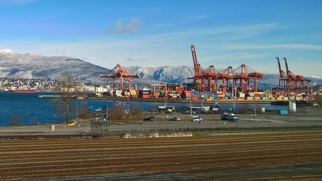 Des chemins de fer longent le port de Vancouver et ses conteneurs assemblés sous des grues.